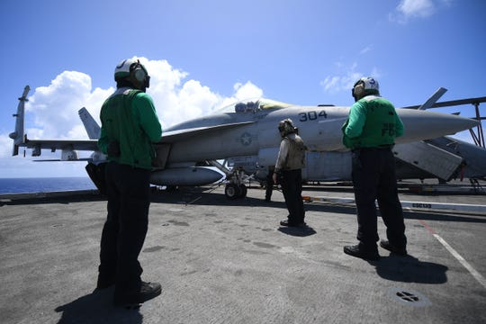 """200524-N-SH180-1025    Sailors inspect an F/A-18E Super Hornet, assigned to the """"Blue Diamonds"""" of Strike Fighter Squadron on the flight deck of the aircraft carrier USS Theodore Roosevelt Sunday, May 24, 2020."""