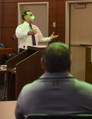 James L. Canto II, acting deputy attorney general for the Office of the Attorney General of Guam, during a court hearing for the double pay lawsuit filed by Guam Police Department officer Steven Thompson, seated, at the Superior Court of Guam in Hagåtña, May 26, 2020.