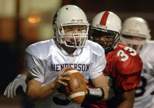 Henderson County quarterback Jeremiah Coursey (9) rolls out for the pass as Owensboro's Jamison Johnson (33) puts the heat on during the 2006 playoff game in Owensboro.