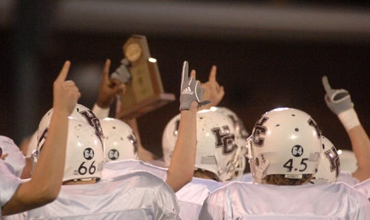 Henderson County players celebrate and hold their trophy high after beating Owensboro in the second round of the 2006 playoffs.