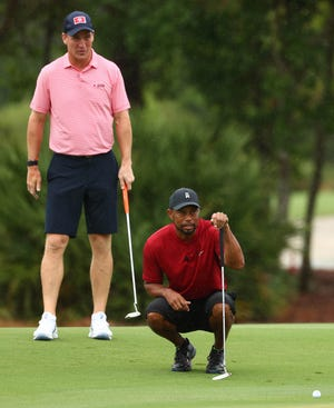 May 24, 2020; Hobe Sound, FL, USA; Tiger Woods and former NFL player Peyton Manning read a putt on the sixth green during The Match: Champions for Charity golf round at the Medalist Golf Club.