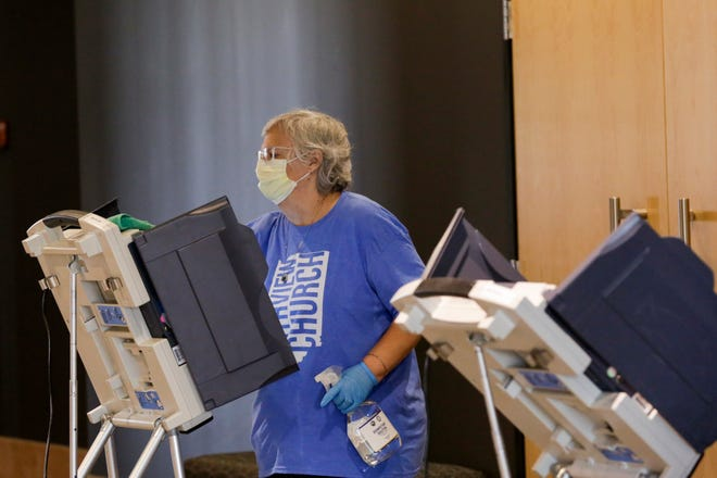 Deb Blake, a poll worker at Northview Church, uses a sanitizer to clean a voting booth as voters cast their ballots ahead of the 2020 Indiana primary, Tuesday, May 26, 2020 in West Lafayette. Early voting began at eight locations across Tippecanoe County including the County Office Building.