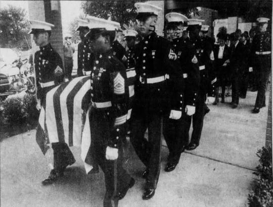 In this Nov. 6, 1983, file photo, Marine pallbearers carry the flag-draped casket of Lex Trahan.