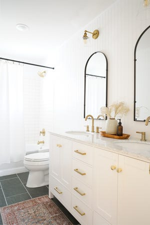 This east-end bathroom remodel features a dual sink, marble-topped vanity with gold faucets, black mirrors, Shaker cabinets, and floor-to-ceiling wainscoting.