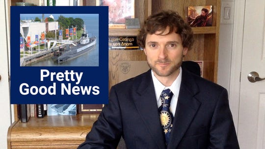 Shane Lee with 'Pretty Good News' shoulder graphic on the 'set' in his spare bedroom.