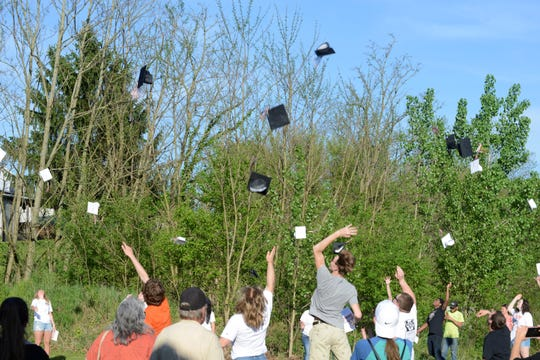 Seniors threw their caps in the air on the field behind the Lucas Community Center.