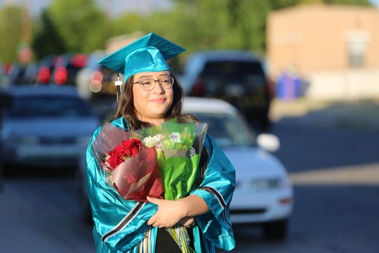 JanileyChavez, 18, who recently graduated from Oñate High School, watches as law enforcement officers parade past her home Friday May 22, 2020, to honor the memory of her father, Hatch Police Officer José Chavez, who was killed in the line of duty in 2016.