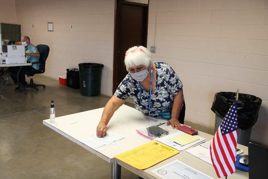 Presiding Judge Carol Garcia arranges masks at the Otero County Fairgrounds during early voting May, 26, 2020.