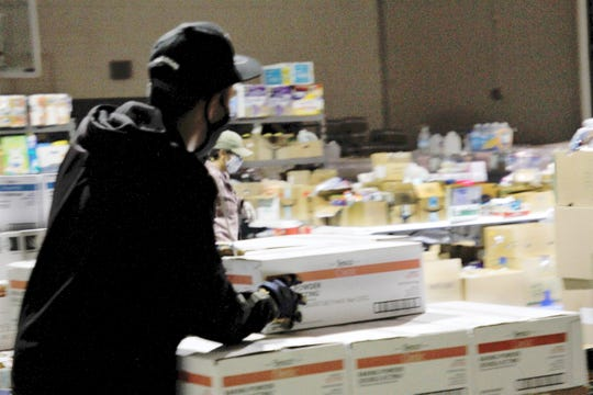 Volunteers stack boxes of food, Monday, May 25, 2020, in a storage facility in Shiprock.