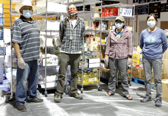 Rep. Anthony Allison, D-Fruitland, Kyle Jim, Breanna Lameman and JoAnn Lameman stand in front of donated supplies in a storage location in Shiprock.