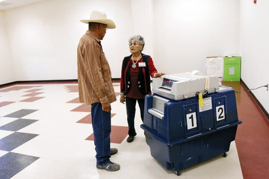 Ray Ballone talks with Roseanna Bahe-Toledo after casting his vote in the Navajo Nation primary election on Aug. 26, 2014 at the Upper Fruitland Chapter house in Upper Fruitland.