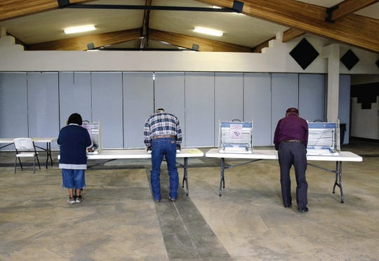 Voters fill in their ballots during the Navajo Nation primary election on Aug. 26, 2014 at the Nenahnezad Chapter house in Nenahnezad.