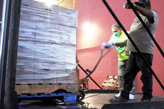 Volunteers with the Arizona chapter of ICNA Relief move pallets of food, Monday, May 25, 2020, into a storage facility in Shiprock.