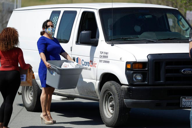 State Assemblywoman Lorena Gonzalez, center, delivers a box of face masks to the Otay Mesa Detention Center, Friday, April 24, 2020, in San Diego.