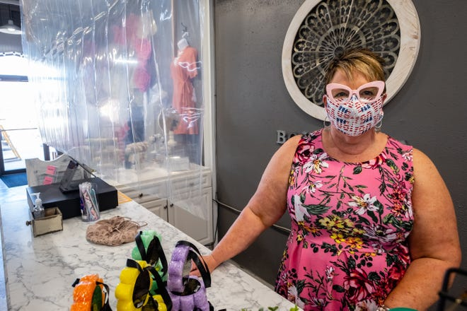 Laura Lyon, who owns Papaya Branch Boutique in downtown Port Huron, poses for a photo behind a plastic sheet hung over the store's counter Tuesday, May 26, 2020.  Hanging the sheet is one of the ways the store is adapting to comply with social distancing guidelines as they begin to reopen.