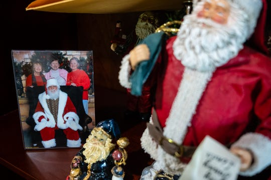 A photograph of Jerry Ayotte, dressed as Santa, with his family, sits on a shelf next to a Santa figure in Ayotte's Croswell home.