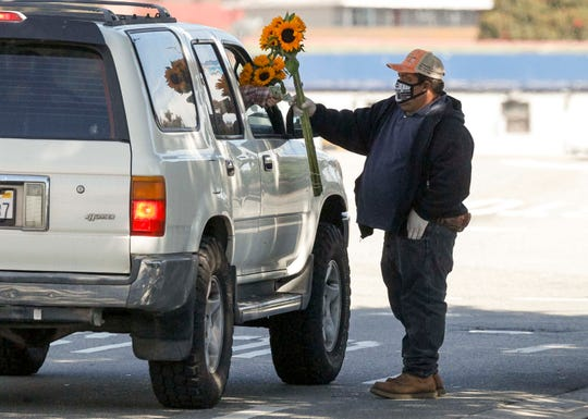 Isidoro Flores Contreras hands a customer a bouquet of sunflowers. He credits Herbalife with helping him walk again, and he believes it will also keep him safe from the novel coronavirus.  May 15, 2020.
