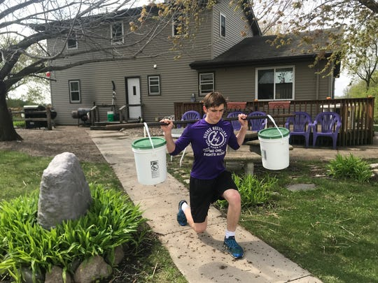 Albany's David Bushman uses water jugs as weights during his lunges. Bushman is finding household items to help with building muscle and staying flexible with the Albany weight room closed during the pandemic.