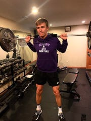 Albany's Jordan Barker lifts weights in his home gym during the distance learning period as he prepares for the next school year of sports.
