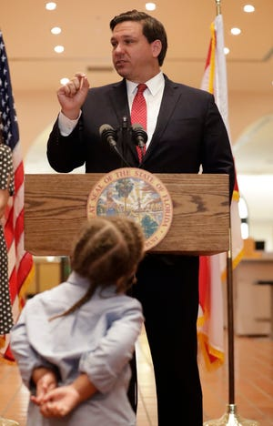 Joshua Fender, 2, foreground, listens to Florida Gov. Ron DeSantis speak after DeSantis introduced Fender's mother, Renatha Francis, during a news conference, Tuesday, May 26, 2020, at the Miami-Dade Public Library in Miami.