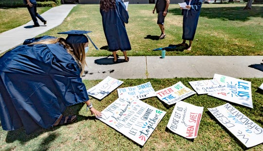 About 40 seniors representing Visalia's four public high schools gather Tuesday, May 26, 2020 at the district office to protest the handling of graduations.