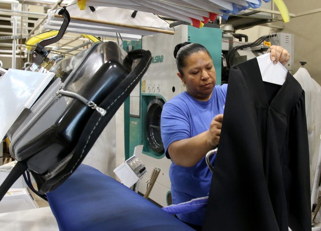 In this 2020 file photo from May, Maria Morales presses a graduation gown at Pressed dry cleaners. The store will again be offering free pressing services for graduation gowns.