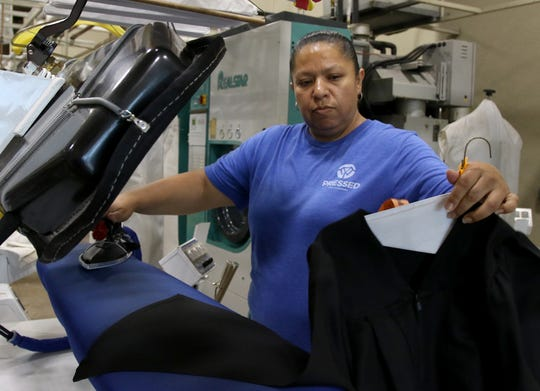 Maria Morales presses a graduation gown Monday, May 26, 2020, at Pressed. The store will press all graduation gowns for free.