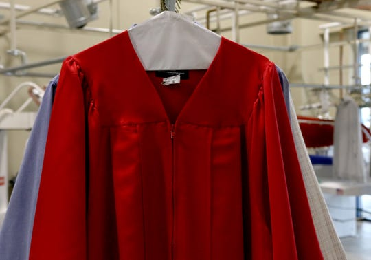 A graduation gown is hanged after being pressed for free Monday, May 26, 2020, at Pressed.