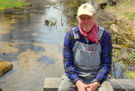 Donald Justin Isherwood in April, 2017, sitting in front of the Isherwood Lateral drainage ditch that he converted into a trout stream.