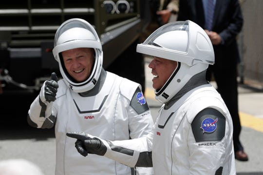 NASA astronauts Douglas Hurley, left, and Robert Behnken wave as they walk out of the Neil A. Armstrong Operations and Checkout Building on their way to Pad 39-A, at the Kennedy Space Center in Cape Canaveral, Fla., Wednesday, May 27, 2020. The two astronauts will fly on a SpaceX test flight to the International Space Station. For the first time in nearly a decade, astronauts will blast into orbit aboard an American rocket from American soil, a first for a private company.
