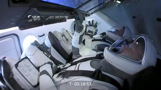 In this Wednesday, May 27, 2020 image from video made available by SpaceX, NASA astronauts Bob Behnken, background left, and Doug Hurley sit in the Crew Dragon capsule as the launch from the Kennedy Space Center in Cape Canaveral, Fla., is aborted due to weather problems. (SpaceX via AP)