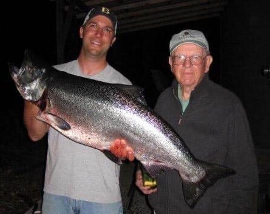 North Kitsap boys basketball coach Scott Orness holds up a king salmon caught by his grandfather John Jensen.