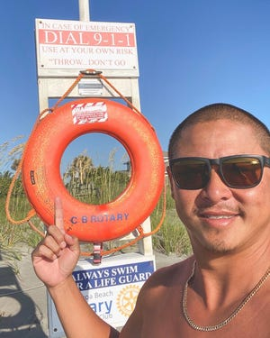 Willy Le stands near the boardwalk at 10th St. South in Cocoa Beach, pointing to the life ring he used to save a man caught in a rip current on May 21.