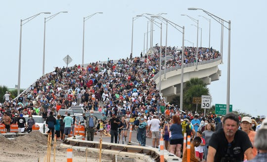 Large crowds of SpaceX spectators gathered at the A. Max Brewer Bridge in Titusville, Florida, hoping to see the first US crew mission in nearly a decade, begin to wander back to their vehicles after the launch scrubbed.