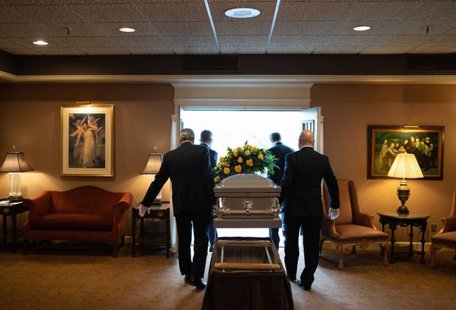 """The first American to die of COVID-19 was in February. The 100,000th death is expected before the end of May. That makes this coronavirus the fastest killer in U.S. history. In this photo, Wujek-Calcaterra & Sons funeral home co-owner Michael J. Calcaterra (middle left) and co-owner Michael F. Wujek (middle right) carry the casket of 90-year-old Janice """"Granny"""" Severini, of Shelby Township, to load into a hearse at their funeral home in Sterling Heights on April 17, 2020, before taking the casket to meet the family for the burial. Severini passed due to COVID-19."""
