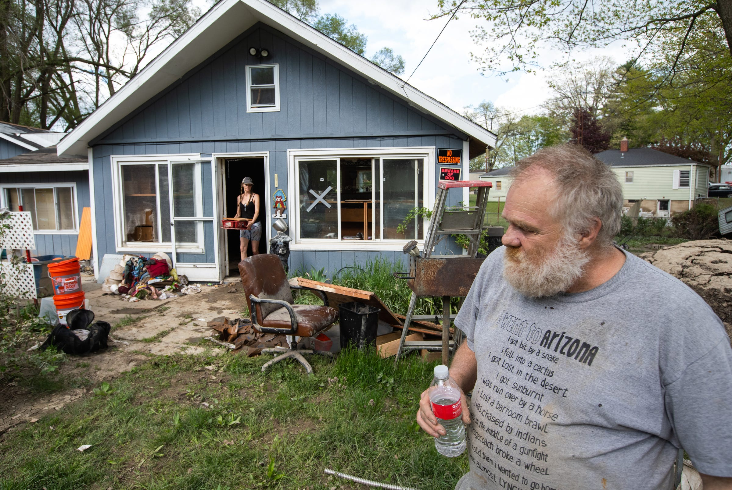 Kenneth Helm walks through his yard in Sanford on Friday, May 22, 2020, as his sister Kim Helm of Standish helps him clear out his home, which was damaged by flood waters three days earlier.