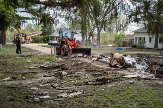 A crew moves debris from the streets on Friday, May 22, as residents cleared damaged items from their homes, which were destroyed by flood waters.