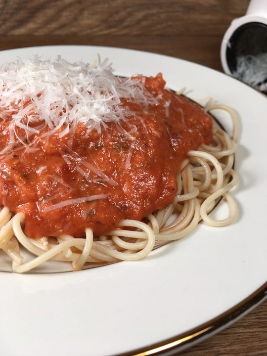 Angel Hair pasta is topped with creamy marinara sauce.