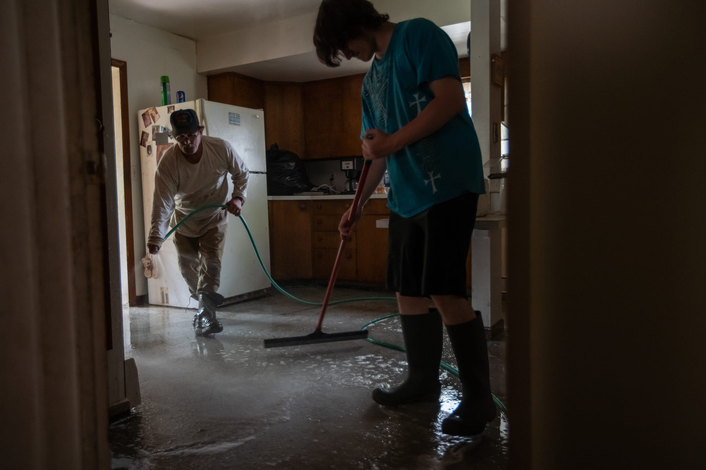Jim Mcguire of Sanford sprays water from a hose across his kitchen floor as his son Robert Mcguire pushes the water down the steps into their flooded basement on Friday, May 22, 2020.