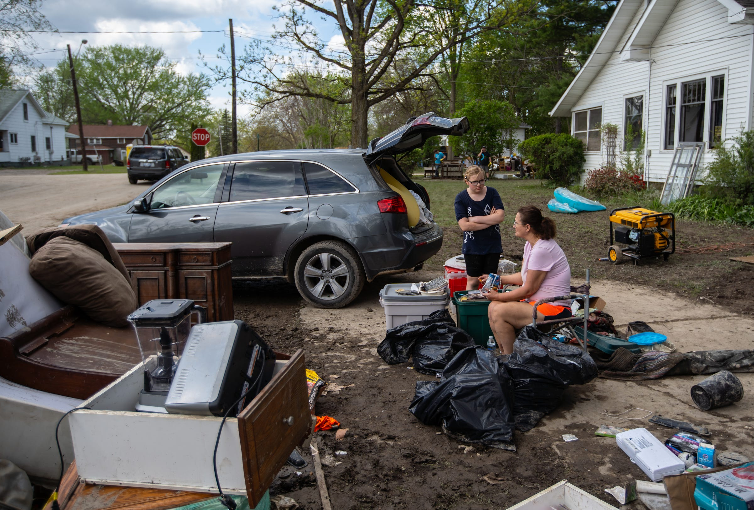 Alexandra Braley (right) and her niece, Skyla Brevis of Beaverton, sit among Braley's damaged belongings in her driveway in Sanford on Friday, May 22, 2020.