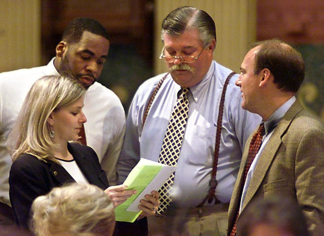 State Representatives, from left to right, Jennifer Faunce (R-Warren), Kwame Kilpatrick (D-Detriot), Bruce Patterson (R-Canton) and Andrew Richner (R-Grosse Pointe Park, huddle on the House floor during Thurday's session.
