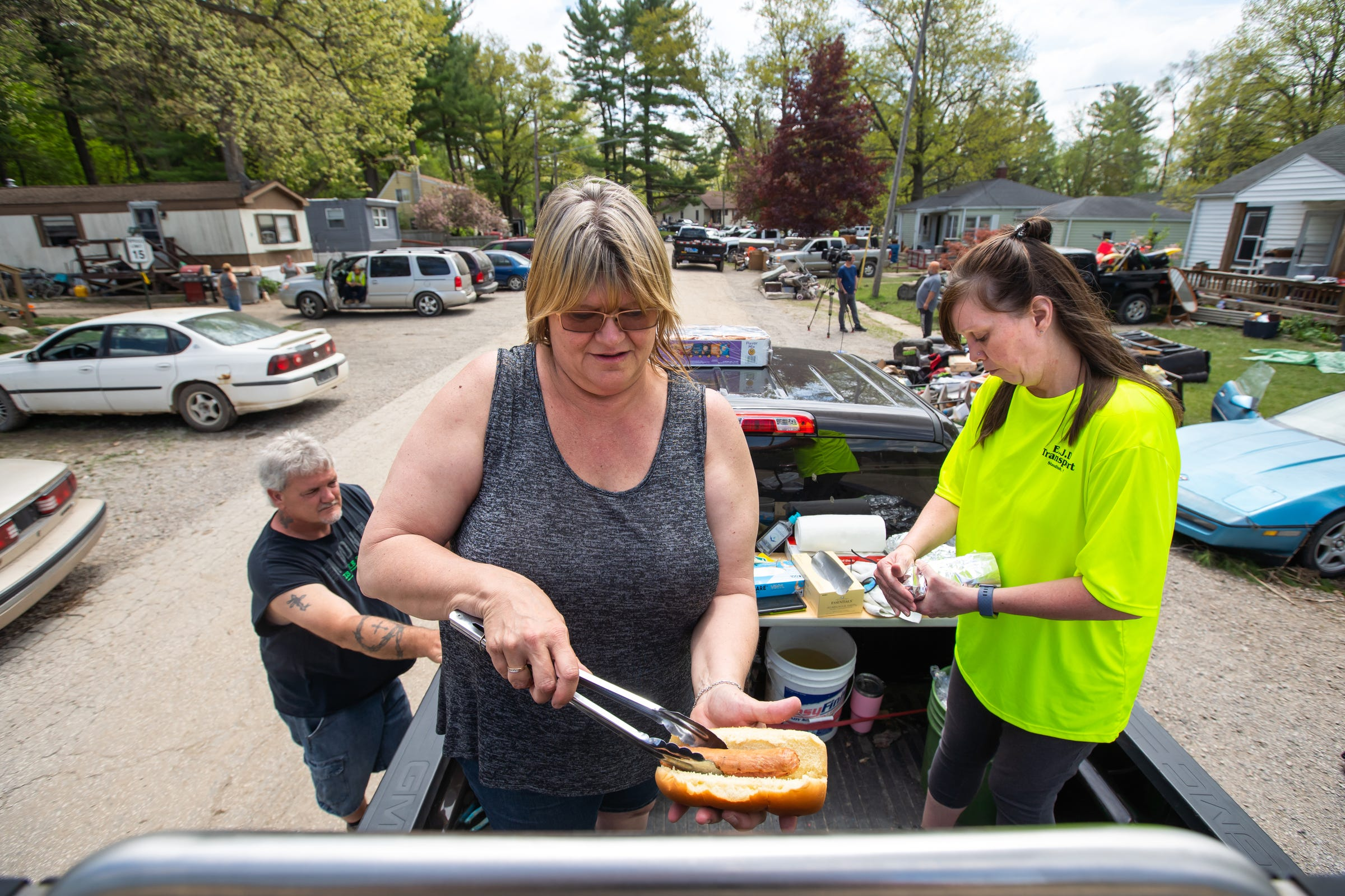 Cyndi Keblbeck of Sanford, and Michele Beck-Bark prepare more hot dogs for residents of the neighborhood surrounding the Sanford Dam who were cleaning out their homes after the historic flood on Friday, May 22, 2020.