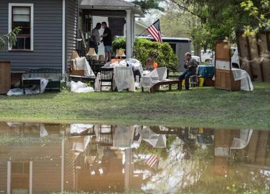 People clear items from a home damaged by flood waters in Sanford on Friday, May 22, 2020.