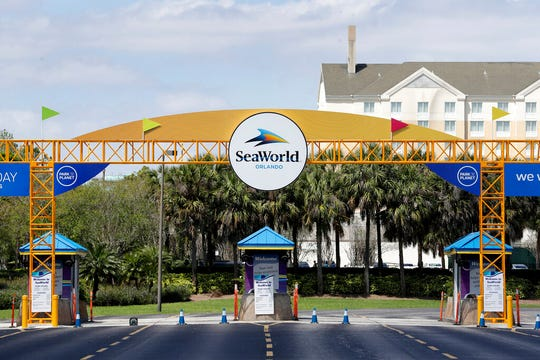 In this March 30, 2020 file photo, the entrance to the SeaWorld Theme park remains closed in Orlando, Fla. SeaWorld and Walt Disney World will reopen in Orlando, Florida, in June and July after months of inactivity because of the coronavirus pandemic, according to plans a city task force approved Wednesday.