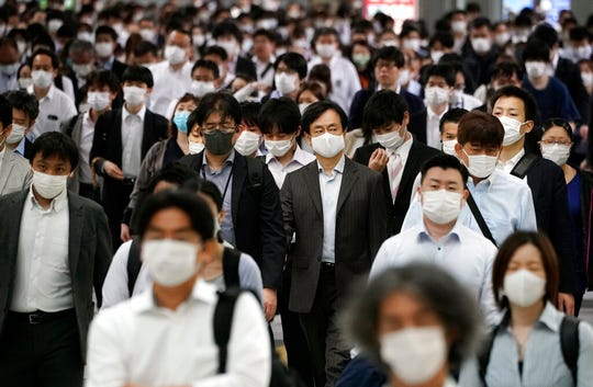A station passageway is crowded with commuters wearing face mask during a rush hour Tuesday, May 26, 2020, in Tokyo. Japanese Prime Minister Shinzo Abe lifted a coronavirus state of emergency in Tokyo and four other remaining prefectures on Monday, May 25, ending the declaration that began nearly eight weeks ago.