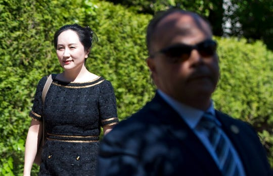 A security guard looks on as Meng Wanzhou, chief financial officer of Huawei, leaves her home to go to British Columbia Supreme Court in Vancouver, Wednesday, May 27, 2020. A Canadian judge ruled Wednesday the U.S. extradition case against Meng can continue to the next stage.