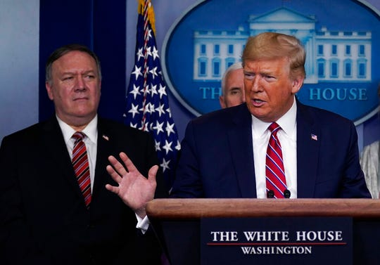 In this March 20, 2020, file photo, Secretary of State Mike Pompeo listens as U.S. President Donald Trump speaks during a coronavirus task force briefing. Pompeo has notified Congress that the Trump administration no longer regards Hong Kong as autonomous from mainland China