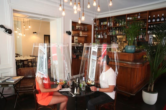A man and a woman demonstrate dining under a plastic shield Wednesday, May 27, 2020 in a restaurant of Paris.