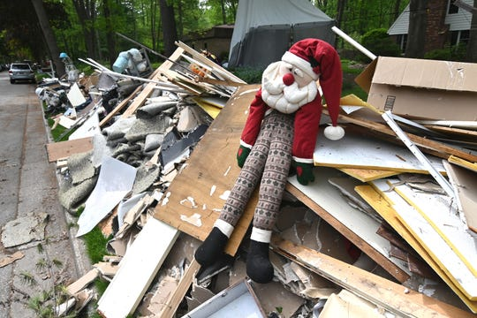 A flood-damaged Santa Claus rest amid debris along Partridge Lane in Midland on Wednesday, May 27, 2020.