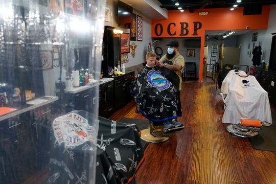 Luis Lopez gives a hair cut to Marty Broser behind a plastic curtain at Orange County Barbers Parlor, Wednesday, May 27, 2020, in Huntington Beach, Calif.